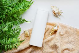 White Bottle Of Brand-free Shampoo On A Beige Towel With Shells And Seaweed. Hair Care Products With