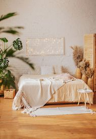 Stylish Bedroom In Bright Boho Style. A Cozy Modern Interior With An Abundance Of Textiles And Livin