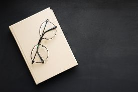 Hardcover Beige Book And Reading Glasses On Black Slate Board.