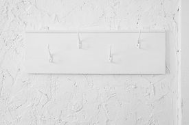 White Wooden Coat Hanger With Hooks On A Textured Wall.