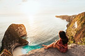 Beautiful Girl Sitting On A High Rock And Looking Out To Sea, Rear View. Girl Sits On The Edge Of Cl