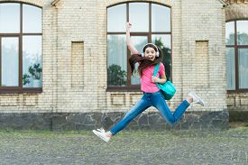 Holidays Are Coming. Happy Child Celebrate Holidays Outdoors. Active Girl Jump To Music. School Holi