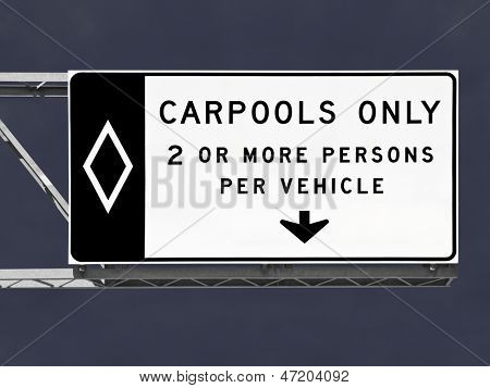 Overhead freeway carpool only sign with storm sky.