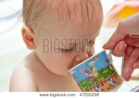 Mom gives to drink from a cup baby
