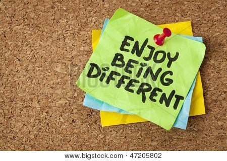 enjoy being different advice - lifestyle or nonconformist concept - handwriting on green sticky note