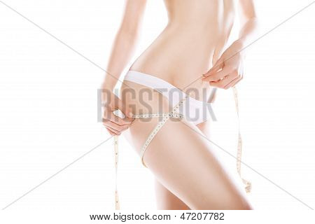 Slimming woman measuring thigh with tape