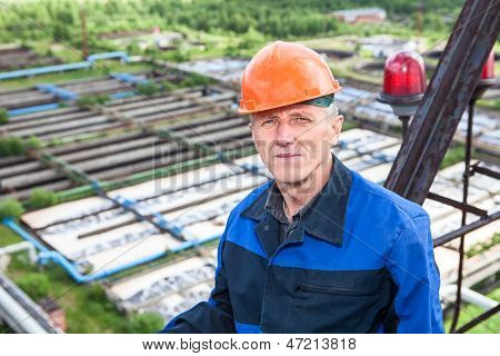 Senior Caucasian Manual Worker Standing Against Water Treatment Plant. Copyspace