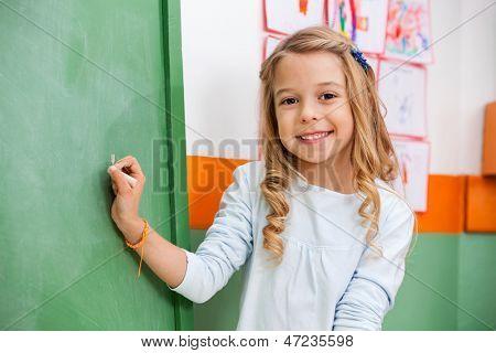 Portrait of cute little girl writing on board in kindergarten