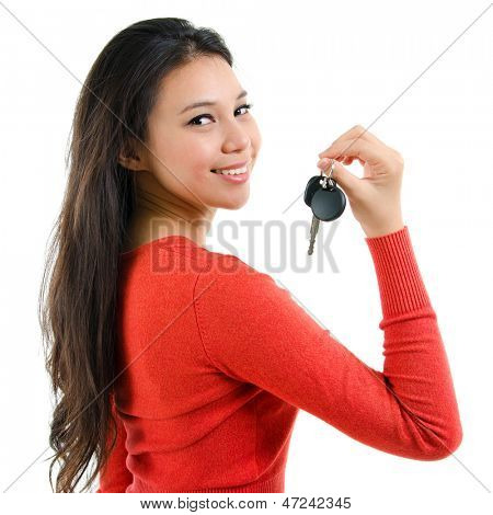 Attractive young woman holding her first own car key isolated on white background. Beautiful mixed race Caucasian Southeast Asian woman model.