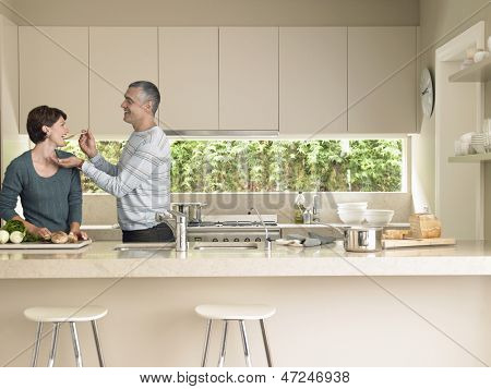 Middle aged man feeding wife at kitchen counter