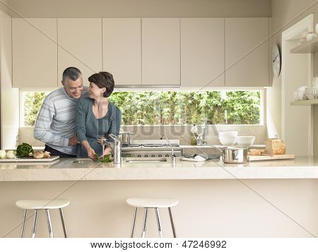 Happy woman washing vegetables while man hugging her from behind in kitchen poster