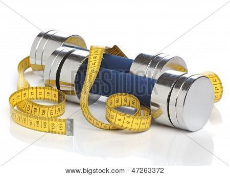 Dumbbells and a measuring tape over white