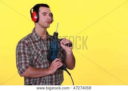 Man with earmuffs and drill poster