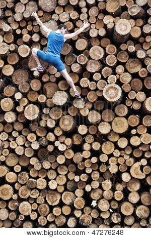 Fit climber going down the large pile of cut wooden logs