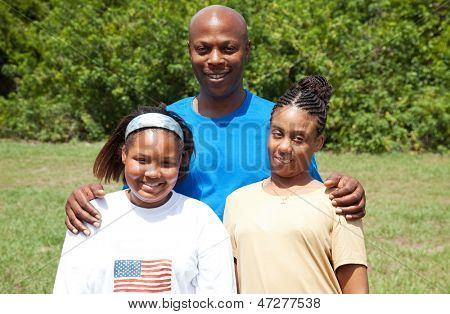 Portrait of a happy, smiling African-american family - father, mother, and daughter.  The mother has cerebral palsy.