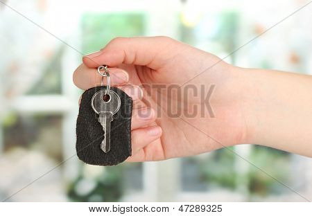 Key with leather trinket in hand on window background
