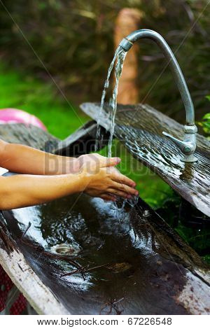 Asian Girl Rinsing Her Hands Under Flowing Water