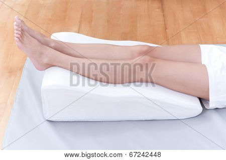 woman's legs lay down on a pillow