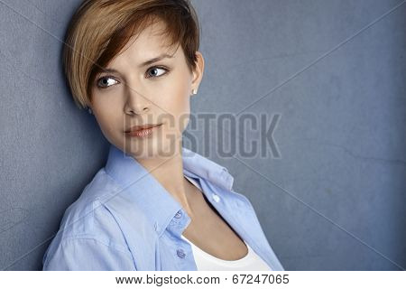 Closeup portrait of attractive young woman leaning to grey wall, smiling