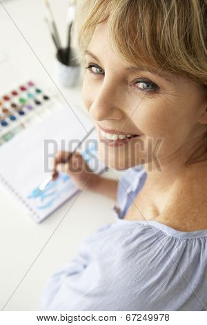 Mid age woman painting with watercolors