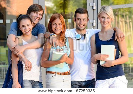 Group of smiling students standing front of college campus summer