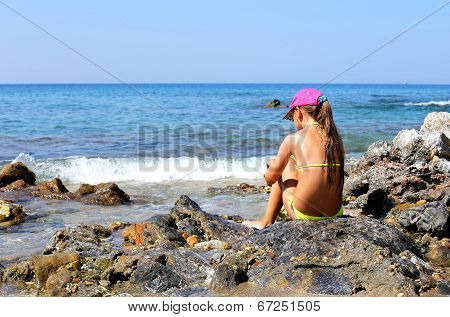 Girl Sitting On A Rock By The Sea