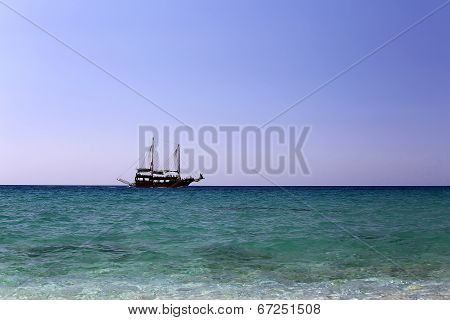 Single Sailing Ship At Open Sea Under Clear Sky