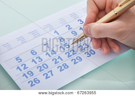 Hand Marking Date 15 On Calendar