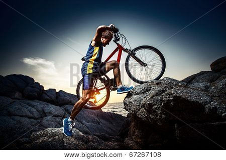 Bicycle rider crossing rocky terrain at sunset