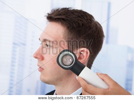 Doctor Examining Businessman With Dermoscope