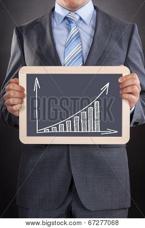 Businessman Showing Bargraph Drawn On Slate