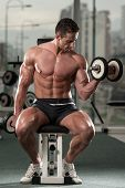 Young Man Working Out Biceps - Dumbbell Concentration Curls poster