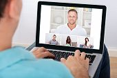 Man having video conference with friends on laptop at home poster