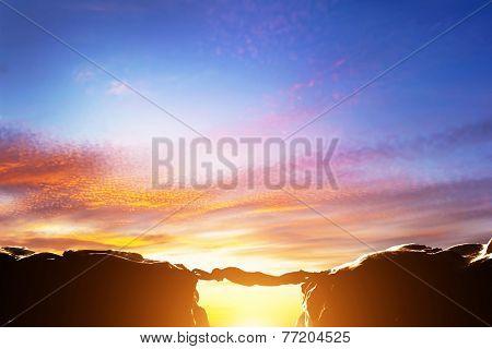 Man serving as a bridge over precipice between two mountains. Sunset, business conceptual