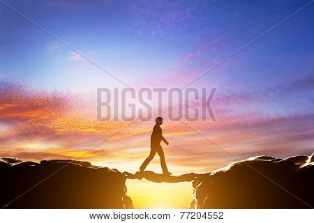 Man walking over precipice between two mountains, another man serving as a bridge. Sunset, business conceptual poster
