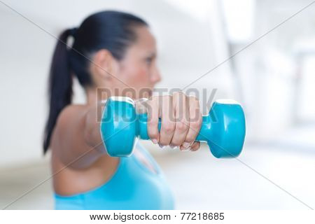 A hand holding blue dumbbell for tricep extension of sporty lady exercising