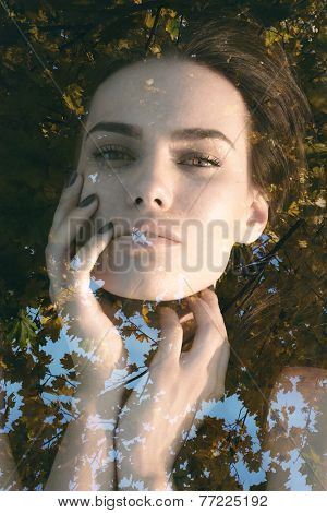 Double exposure portrait of young woman covering her eyes with hair combined with photograph of nature
