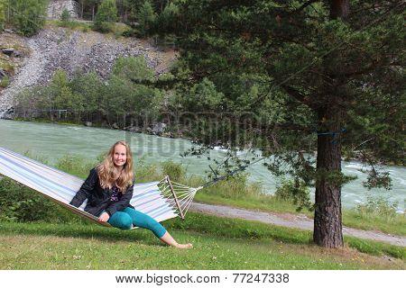 A girl sitting on the hammock.