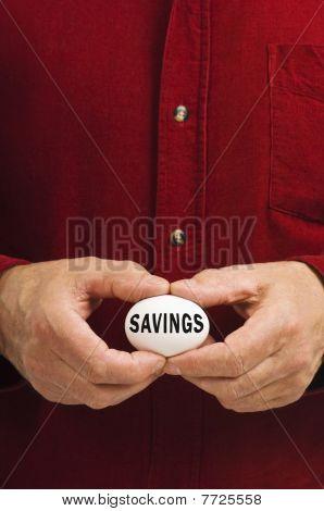 Savings Written On Nest Egg Held By Man