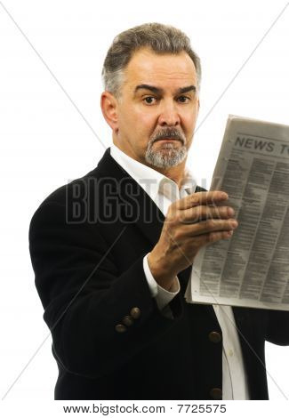 Mature Man Holds A Newspaper, Looking Serious.