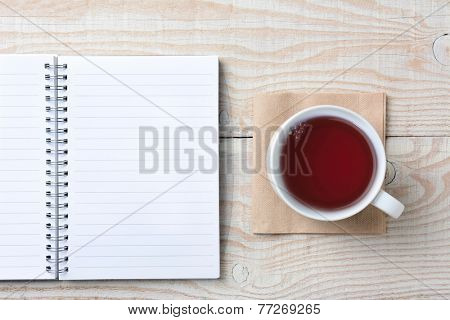 Closeup of an open notebook and a cup of hot tea on a rustic white wood table. High angle shot in horizontal format.