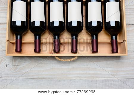 Overhead shot of a case of red wine bottles with blank labels  on a rustic white wood table with copy space at the bottom. Horizontal format.