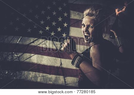 Punk girl against USA flag with brass knuckles and Molotov cocktail