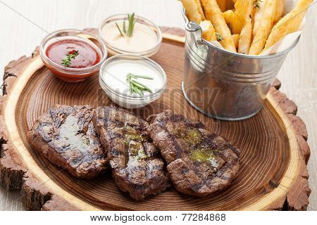 Portion Of Bbq Beef Filet Mignon With  Sauces And Fried Potatoes
