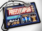 Medical Tablet with the Diagnosis of Preeclampsia on the Display and a Black Stethoscope on White Background. poster