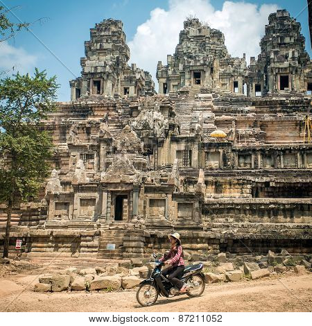 Angkor Wat, Cambodia - March 13, 2014: Unidentificate woman riding motorbike in front of old temple at Angkor wat complex