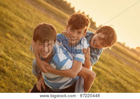 Portrait of three happy cheerful brothers at sunset outdoor poster