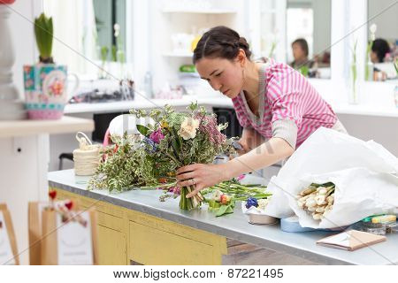 Masterclass of smiling florist at work with bunch of flowers poster