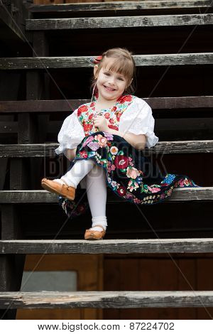 Sitting Little Girl In Traditional Costume