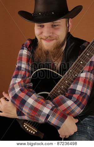 Portrait of the young man of the cowboy with a guitar